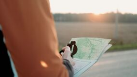 Hiking Man Using Navigation Map and Compass. Man explorer searching direction with compass in sunset. Man hand holding