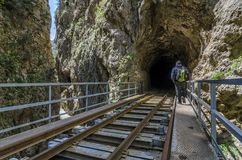 Hiking at Vouraikos gorge following the Diakopto–Kalavrita rack railway route. Peloponnese - Greece. A man with backpack is entering a tunnel while stock photos