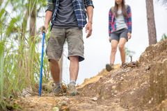 Hiking man and woman with backpack and trekking boots on the bright green moss passage trail in forest stock image
