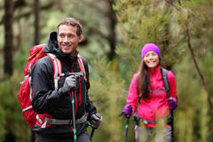 Hiking man and woman on hike in forest on hike. Hiking men and women on hike in forest trekking. Couple on adventure trek in beautiful forest nature Stock Photos
