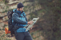 Hiking map man. Man with map exploring wilderness on trekking adventure Royalty Free Stock Photography