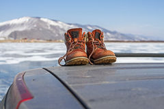 Hiking massive boots on the roof of the car on the beautiful mountains background on Lake Baikal in winter. Hiking massive boots on the roof of the car on the Stock Photography