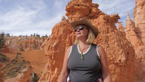 Hiking Mature Woman Enjoy The Fantastic Views Of Bryce Canyon Utah Usa. Hiking caucasian mature fat woman tourist with a hat and sunglasses standing on the stock video footage