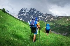 Hiking. Men on hiking trail. Trekking in mountains. Tourists with backpack hike to mountain peak royalty free stock photography