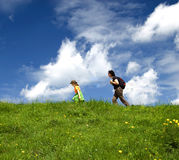 Hiking. Mother and daughter hiking through a lush green landscape Stock Photos