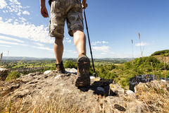 Hiking on a mountain trail. Hiker hiking on a mountain trail with distant views of countryside in summer sunshine Royalty Free Stock Images