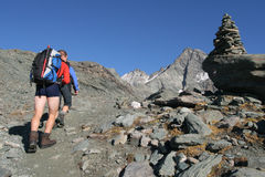 Hiking in the mountains. Hikers with backpacks in rocky mountains stock photography