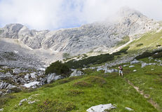 Hiking through the Mountains. A backpacker hikes across a small meadow in the granite mountains of the Dolomites in northern Italy Stock Photography