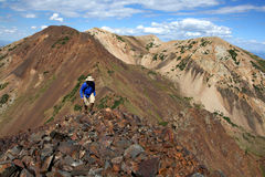 Hiking in mountains. Male hiker walks alone along a high mountain ridge Royalty Free Stock Photo