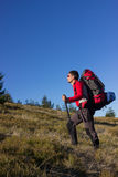 Hiking in the mountains. Man hiking in the mountains with a backpack and tent Stock Images