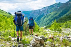 Hiking in mountains. Men hike in mountain trail. Tourists with backpacks walking on trek. Trekking in Caucasus. Hiking in mountains. Men hike in mountain trail royalty free stock photography