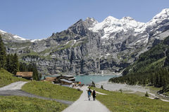 Hiking in the mountains. Oeschinen Lake (German: Oeschinensee) in the Bernese Oberland, Switzerland, 4 kilometres (2.5 mi) east of Kandersteg in the Oeschinen Stock Photo