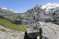 Hiking in the mountains. Oeschinen Lake (German: Oeschinensee) in the Bernese Oberland, Switzerland, on a summer day Stock Image