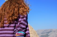 The girl is looking into the distance. hiking in the mountains. stock photo