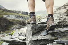 Hiking over rocks on a mountain trail stock photo