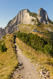 Hiking path and guesthouse. Hiking path through rocky mountainous terrain with rest house and strange rock formations, Switzerland Stock Images