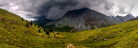 Hiking path in mountain valley. Approaching storm front Royalty Free Stock Images