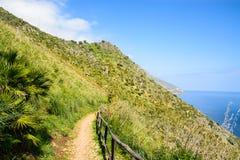 Hiking Path At Seaside. Hiking path on green hillside next to the Mediterranean sea. Sicily, San Vito Lo Capo, Gran Riserva Dello Zingaro Stock Image