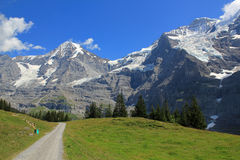 Hiking path to Kleine Scheidegg with the famous mountains Jungfrau and Mönch in Switzerland. View at the Mönch and Jungfrau with glaciers in Berner Oberland Stock Photo