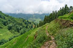 Hiking path with view from above on countryside mountain valley. With rice terraces and fields on sunny day Royalty Free Stock Photo