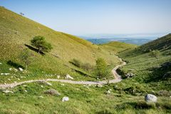 Hiking path winding between the green hills royalty free stock images