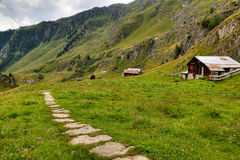 Hiking path with wooden huts, Switzerland Royalty Free Stock Images