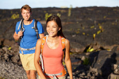 Hiking people - couple walking on lava field. On Hawaii. Tourists hikers on hike near Kilauea volcano around Hawaii volcanoes national park, USA Royalty Free Stock Photo