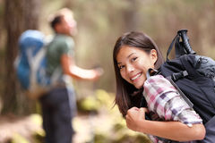 Hiking people friends - girl hiker in forest. Hiking people. Woman hiker smiling in forest with male hiker in the background. Mixed-race Asian Caucasian female Royalty Free Stock Photo