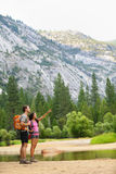 Hiking people on hike in mountains in Yosemite. Hikers young couple pointing looking up in mountain landscape in Yosemite National Park, California, USA Stock Photos