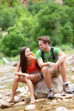 Hiking people - hiker couple happy in Zion Park. Hiking people - hiker couple happy in Zion National Park talking and resting. Young women and men hiker sitting Stock Photography