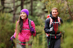 Hiking people - hikers trekking in forest on hike. Couple on adventure trek in beautiful forest nature. Multicultural Asian women and Caucasian men living stock photography