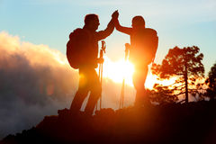 Hiking people reaching summit top high five. Hiking people reaching summit top giving high five at mountain top at sunset. Happy hiker couple silhouette. Success Stock Photography