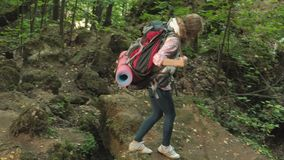 Hiking people - tourists couple at sunset in the mountains. Traveler woman hiking on foot with backpacks in a trail at. Sunset in the mountains 4k stock footage