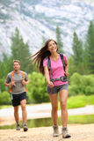Hiking people - couple hikers happy in Yosemite. Hiking people. Young couple of hikers walking. Woman smiling happy in foreground with men and mountains in Stock Image