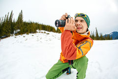 Hiking photographer taking pictures. Treking  in the winter mountains Stock Image