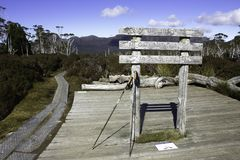 Hiking poles lean against a sign to side tracks off Tasmania`s Overland Track. While the main track runs through the image stock images