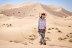 Hiking in Sahara. A girl walking through dunes of Sahara desert royalty free stock images