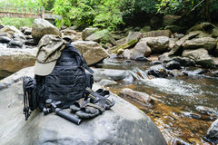 Hiking sandals, backpack, cap and camera on a big rock Royalty Free Stock Photo