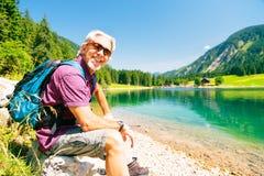 Hiking Senior Man. Taking a rest by a mountain lake royalty free stock image
