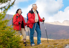 Hiking seniors 11. Cute seniorcouple hiking in an autumn mountainlandscape royalty free stock images