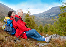 Hiking seniors 2. Cute seniorcouple hiking in an autumn mountainlandscape royalty free stock photography