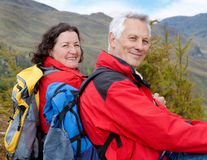Hiking seniors 3. Cute seniorcouple hiking in an autumn mountainlandscape royalty free stock image