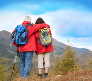 Hiking seniors 7. Cute seniorcouple hiking in an autumn mountainlandscape. Lots of blue sky for text stock photo