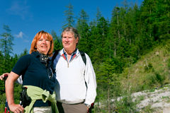 Hiking Seniors. A senior couple is hiking in the mountains royalty free stock photo