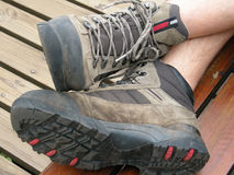 Hiking shoes. Two feet of a Caucasian white adult man wearing fashionable comfortable hiking boots while taking a break outdoors Royalty Free Stock Images