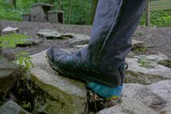 Hiking shoes, close up hiker outdoors walking over rocks Stock Photography