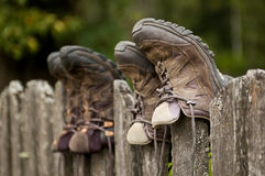 Hiking shoes on a fence. Hiking shoes on a wooden fence Royalty Free Stock Photography