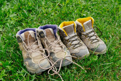 Hiking shoes in the grass. Two pairs of hiking shoes in the grass Royalty Free Stock Images