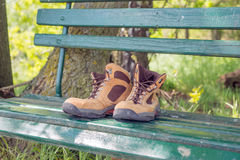 Hiking shoes on green bench Stock Photos