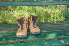 Hiking shoes on green bench Royalty Free Stock Photography